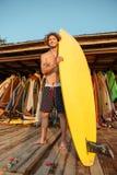 Επαγγελματικό νέο surfer που παίρνει τον πίνακα έτοιμο για την κυματωγή Στοκ Εικόνα