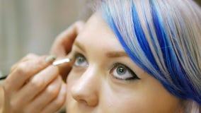 Επαγγελματικό πρόσωπο makeup ένα νέο κορίτσι με την μπλε τρίχα φιλμ μικρού μήκους