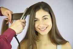 Επαγγελματικό σιδέρωμα κομμών τρίχας μακρυμάλλες της χαριτωμένης χαμογελώντας γυναίκας στοκ εικόνα