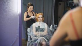 Επαγγελματικό στούντιο ομορφιάς τρίχας χρωματίζοντας Το κορίτσι στην καρέκλα πελατών που εξετάζει την αντανάκλαση στον καθρέφτη φιλμ μικρού μήκους
