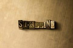 ΕΠΑΝΔΡΩΣΗ - κινηματογράφηση σε πρώτο πλάνο της βρώμικης στοιχειοθετημένης τρύγος λέξης στο σκηνικό μετάλλων Στοκ Εικόνα
