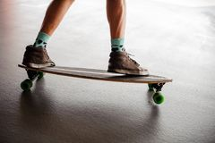 Επανδρώνει τα πόδια στα πάνινα παπούτσια που στέκονται σε ένα longboard Στοκ εικόνα με δικαίωμα ελεύθερης χρήσης
