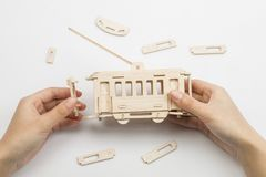 Επανδρώνει τα χέρια συγκεντρώνοντας το ξύλινο trolleybus παιχνίδι Στοκ Φωτογραφία