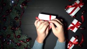 Επανδρώνει το περικάλυμμα χεριών ένα δώρο Μαύρο υπόβαθρο των Χριστουγέννων που εξωραΐζεται με τα μπιχλιμπίδια και τα φω'τα απόθεμα βίντεο