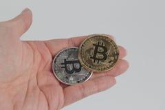 επανδρώνει το χέρι κρατά ένα χρυσό και ασημένιο νόμισμα bitcoin Στοκ Εικόνες