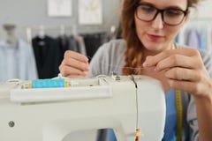 Επαν-πέρασμα κλωστής σε βελόνα της ράβοντας μηχανής Στοκ Εικόνα