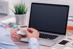 Επανδρώνει τα χέρια με το φλιτζάνι του καφέ μπροστά από το ανοικτό πρότυπο lap-top στο γραφείο γραφείων στοκ εικόνες