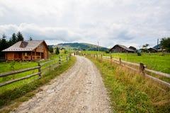 Επαρχία με τα ξύλινα σπίτια και τα αμμώδη δάση οδικών κοντινά βουνών Στοκ Φωτογραφίες