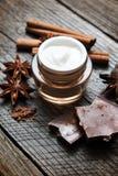 Επεξεργασία δερμάτων σοκολάτας Καλλυντικό βάζο με το λοσιόν, κακάο, γλυκάνισο, ραβδιά κανέλας Στοκ Φωτογραφίες