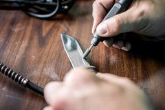 Επεξεργασία της λεπίδας μαχαιριών με τον ειδικό εξοπλισμό για να το καταστήσει πολύ αιχμηρό στοκ εικόνα