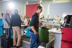 Επιβάτες αερογραμμών που ζυγίζουν τις αποσκευές τους στον αερολιμένα Στοκ φωτογραφία με δικαίωμα ελεύθερης χρήσης