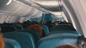 Επιβάτες μέσα στην καμπίνα της συνεδρίασης αεροσκαφών επιβατών στις καρέκλες κατά τη διάρκεια της πτήσης φιλμ μικρού μήκους