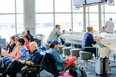 Επιβάτες που κάθονται στην περιμένοντας περιοχή τροφής Στοκ Εικόνες