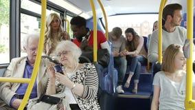 Επιβάτες που χρησιμοποιούν τις κινητές συσκευές στο ταξίδι λεωφορείων απόθεμα βίντεο