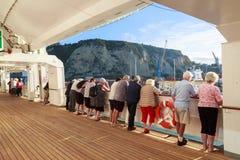 Επιβάτες σε ένα σκάφος της γραμμής κρουαζιέρας, που εξετάζει έξω το λιμένα στοκ φωτογραφία με δικαίωμα ελεύθερης χρήσης