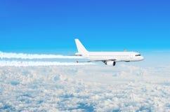 Επιβάτης αεροπλάνου που πετά σε επίπεδο πτήσης με τα contrails των μηχανών επάνω από το μπλε ουρανό σύννεφων Στοκ Εικόνες