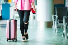 Επιβάτης αεροπλάνων κινηματογραφήσεων σε πρώτο πλάνο με τα διαβατήρια και το πέρασμα τροφής και ρόδινες αποσκευές σε ένα σαλόνι α Στοκ Εικόνες