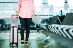 Επιβάτης αεροπλάνων κινηματογραφήσεων σε πρώτο πλάνο με τα διαβατήρια και το πέρασμα τροφής και ρόδινες αποσκευές σε ένα σαλόνι α Στοκ εικόνα με δικαίωμα ελεύθερης χρήσης