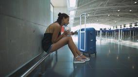 Επιβάτης, γυναίκα που εγκαθιστά στον αερολιμένα, που περιμένει την πτήση της που χρησιμοποιεί το τηλέφωνό της απόθεμα βίντεο