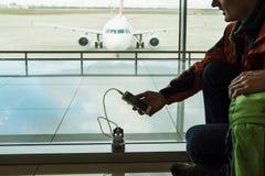 Επιβάτης που χρεώνει την κινητή συσκευή στο σαλόνι του αερολιμένα Στοκ φωτογραφία με δικαίωμα ελεύθερης χρήσης