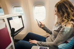 Επιβάτης στην επιχειρησιακή κατηγορία αεροπλάνου με το smartphone Στοκ Φωτογραφία