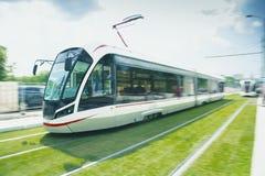 Επιβατική αμαξοστοιχία υψηλής ταχύτητας στην κίνηση στο σιδηρόδρομο Ένα τραμ με την επίδραση θαμπάδων κινήσεων στοκ εικόνα