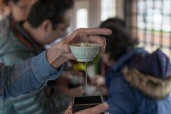Επιβατών δοκιμάζοντας χάρη φλυτζανιών χρήσης παραδοσιακή (ιαπωνικό καθαρό ρύζι W Στοκ Φωτογραφίες