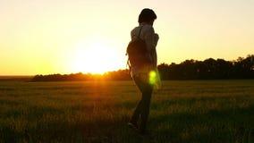 Επιβραδυνμένη κυκλοφορία ενός κοριτσιού που ντύνει ένα σακίδιο πλάτης και που περπατά κατά μήκος ενός πράσινου χορτοτάπητα σε ένα απόθεμα βίντεο