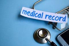 Επιγραφή ιατρικών αναφορών με την άποψη του στηθοσκοπίου, eyeglasses και του smartphone στο μπλε υπόβαθρο στοκ εικόνες