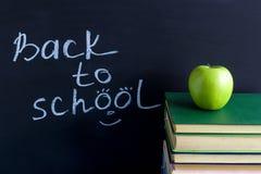 Επιγραφή πίσω στο σχολείο Apple στα βιβλία σωρών Στοκ Φωτογραφία