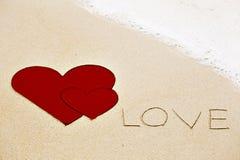 Επιγραφή της αγάπης που γράφεται στην υγρή κίτρινη άμμο παραλιών Στοκ Εικόνες