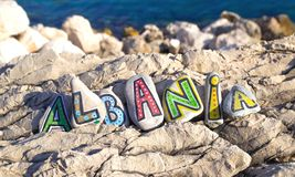 Επιγραφή της Αλβανίας φιαγμένη από χρωματισμένες πέτρες στους βράχους, υπόβαθρο θάλασσας Στοκ Φωτογραφία
