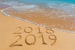 επιγραφή του 2019 του 2018 που γράφεται στην υγρή κίτρινη άμμο παραλιών που είναι στοκ εικόνα
