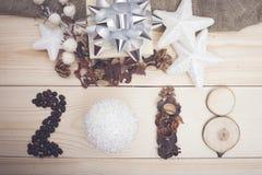 επιγραφή του 2018 των φασολιών καφέ, μιας σφαίρας Χριστούγεννο-δέντρων, ξηρών λουλουδιών και ξύλινων φετών στοκ φωτογραφία με δικαίωμα ελεύθερης χρήσης