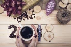 επιγραφή του 2018 των φασολιών καφέ, χέρια της γυναίκας που κρατά μια κούπα καφέ και ξύλινες φέτες, πορφυρά παιχνίδια Χριστουγένν Στοκ Εικόνες