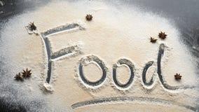 Επιγραφή τροφίμων στο αλεύρι σε ένα ξύλινο μαύρο υπόβαθρο απόθεμα βίντεο