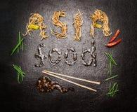 Επιγραφή τροφίμων της Ασίας των νουντλς και της σάλτσας με chopstick και του κόκκινου τσίλι στο σκοτεινό υπόβαθρο πλακών στοκ εικόνα με δικαίωμα ελεύθερης χρήσης