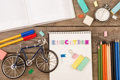 επιγραφή & x22 education& x22 , πρότυπο ποδηλάτων, χρονόμετρο με διακόπτη, βιβλίο, σημειωματάριο και άλλα χαρτικά στον καφετή ξύλ στοκ εικόνες