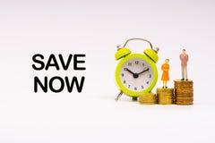 Επιγραφή NOW SAVE γραπτή, ξυπνητήρι, νομίσματα και μικρογραφία επιχειρηματιών στοκ φωτογραφία με δικαίωμα ελεύθερης χρήσης