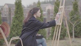 Επιδέξια χρώματα καλλιτεχνών στον καμβά στο κατώφλι Όμορφο ενθουσιώδες κορίτσι που συμμετέχεται στη δημιουργικότητα έμπνευση απόθεμα βίντεο
