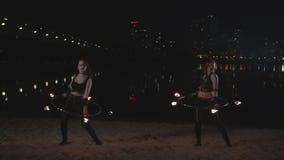Επιδέξια firegirls που στρίβουν τις στεφάνες πυρκαγιάς πέρα από το σώμα απόθεμα βίντεο