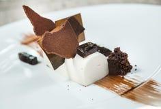 Επιδόρπιο - κέικ ριπών σοκολάτας που διακοσμείται με τα κομμάτια σοκολάτας Άσπρη σοκολάτα Πιάτο του εστιατορίου Στοκ εικόνα με δικαίωμα ελεύθερης χρήσης