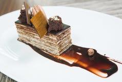 Επιδόρπιο - κέικ ριπών σοκολάτας που διακοσμείται με τα κομμάτια σοκολάτας Και εξεντερισμένο κακάο και σκόνη Πιάτο του εστιατορίο Στοκ εικόνες με δικαίωμα ελεύθερης χρήσης
