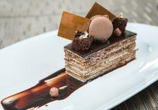 Επιδόρπιο - κέικ ριπών σοκολάτας που διακοσμείται με τα κομμάτια σοκολάτας Και εξεντερισμένο κακάο και σκόνη Macaroons άνωθεν πιά Στοκ Εικόνες