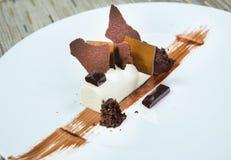 Επιδόρπιο - κέικ ριπών σοκολάτας που διακοσμείται με τα κομμάτια σοκολάτας Και εξεντερισμένο κακάο και σκόνη Πιάτο του εστιατορίο Στοκ Φωτογραφία