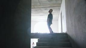 Επιζημένο άτομο που περπατά στο σκοτάδι στο εγκαταλειμμένα κτήριο και τα ολισθήματα σε ένα zombie Zombie που παρατηρεί τον και πο φιλμ μικρού μήκους