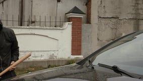 Επιθετικός βάνδαλος στη μάσκα και κουκούλα που πηγαίνει να συντρίψει το αυτοκίνητο με το ρόπαλο του μπέιζμπολ στην οδό απόθεμα βίντεο