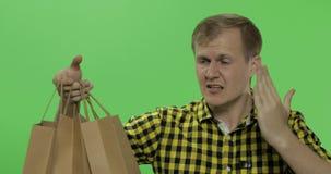 0 επιθετικός νεαρός άνδρας με τις τσάντες αγορών E απόθεμα βίντεο
