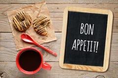 Επιθυμεί bon appetit στο μικρό πίνακα, το φλυτζάνι καφέ και τα μπισκότα Στοκ Φωτογραφία