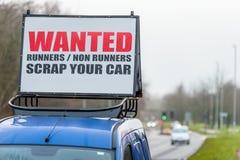 Επιθυμητό απόρριμα μη δρομέων δρομέων το σημάδι αυτοκινήτων σας στη στέγη αυτοκινήτων δίπλα στο βρετανικό αυτοκινητόδρομο Στοκ Εικόνες